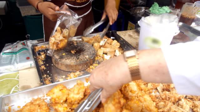 Preparing fried snack for customer video