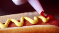 Preparing Hot Dog with Mustard and Ketchup video