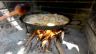 Preparing large dish of paella with firewood video