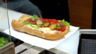 Preparing sandwich with ham and swiss cheese sandwich on brown bread video