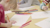 4K: Preschool children drawing and coloring in their classroomPreschool teacher teaching her children about coloring drawing. Cute girl and boys are sitting by the table and teacher talking to them. Teacher using sharpener. Models in this shot are part of video