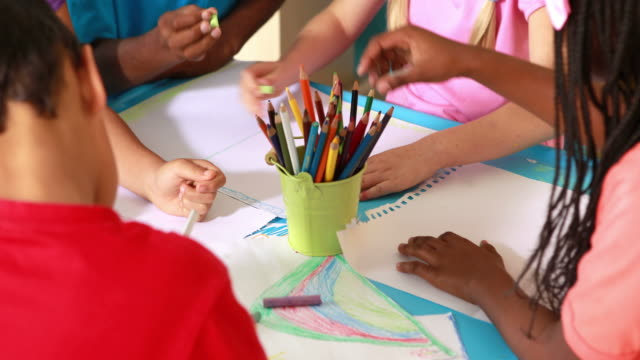 Preschool class drawing at table in classroom video