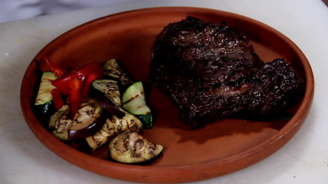 Presentation of sizzling hot steak just taken off the grill video