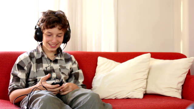 Pre-teen boy listening to  an mp3 player video