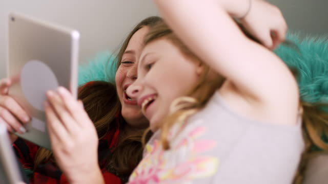 Preteen friends using their tablets together at home video