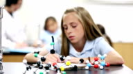 Preteen student analyzing molecular models in class video