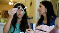 Preteen student examining molecule science model during home school class with mother video