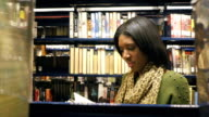 Pretty African American young female teacher searches for book in local public library video