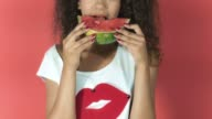 Pretty Afro-American girl eating watermelon on red background. video