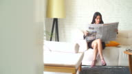 4K:A pretty asian business woman reading the newspaper in her room. video