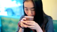 pretty asian girl drinking hot chocolate on tea time video