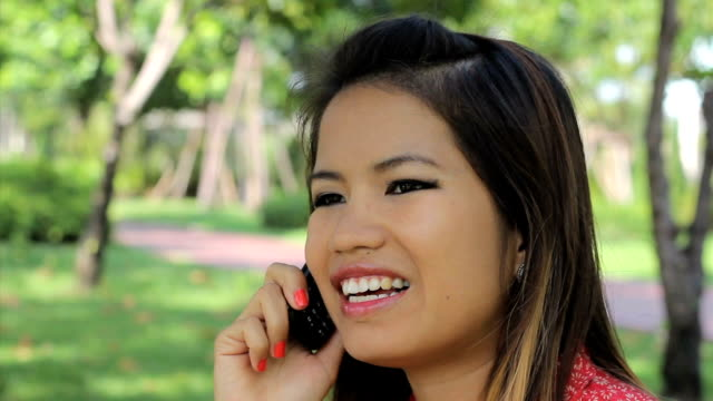 Pretty Asian Girl Having A Happy Cell Phone Call video