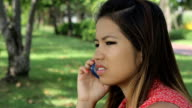 Pretty Asian Girl Having A Serious Cell Phone Call video