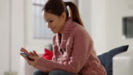Pretty asian girl reading sms on smarthphone at home video