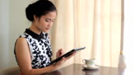 Pretty Asian Woman Using Tablet In Cafe video