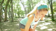 Pretty blonde athletic woman warming up before off road running video