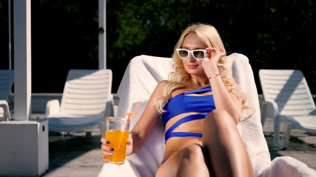 Pretty blonde drink the juice near swimming pool video