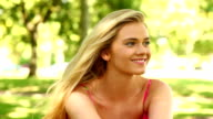 Pretty blonde relaxing in the park video