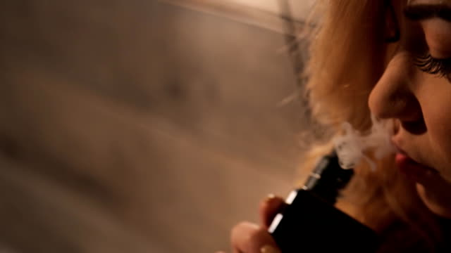 Pretty blonde woman expires clubs of white fragrant smoke video