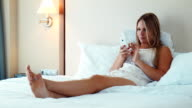 Pretty blonde woman lying in bed and use smartphone video
