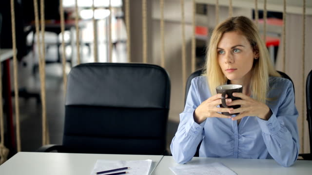 Pretty blonde woman sits at table in office and drinks coffee video