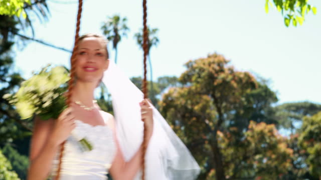 Pretty bride sitting on a swing smiling at camera video