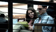 Pretty brunette girl and man in black rim glasses using tablet pc together in a cafe. FullHD shot video