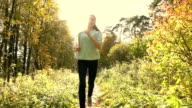 Pretty brunette girl with ponytail running in autumn forest. Sunny day, blazing sun. Super slow motion steadicam shot video