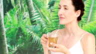 Pretty brunette holding a cup of herbal tea video
