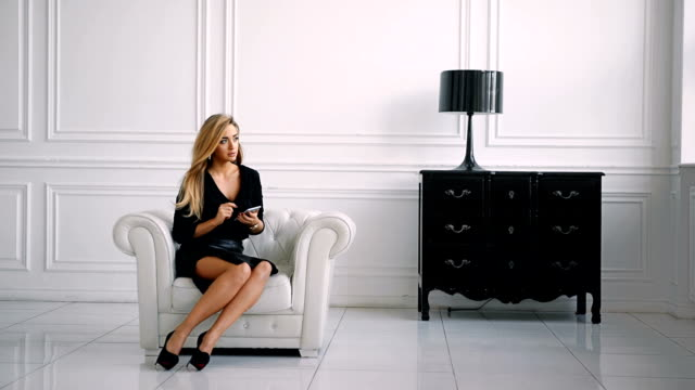 Pretty businesswoman in casual clothes is using a smartphone and smiling, sitting in chair against modern white background. video