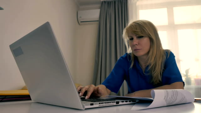 Pretty businesswoman working as freelancer with laptop at home video