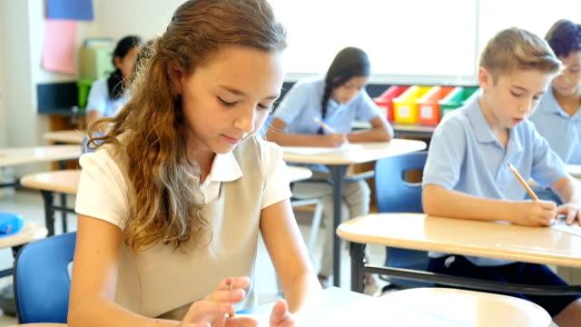 Pretty Caucasian schoolgirl works on assignment in class video