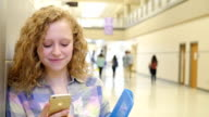 Pretty Caucasian teen girl with blonde curly hair texting on phone in high school video