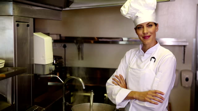 Pretty chef standing beside a large steaming pot video