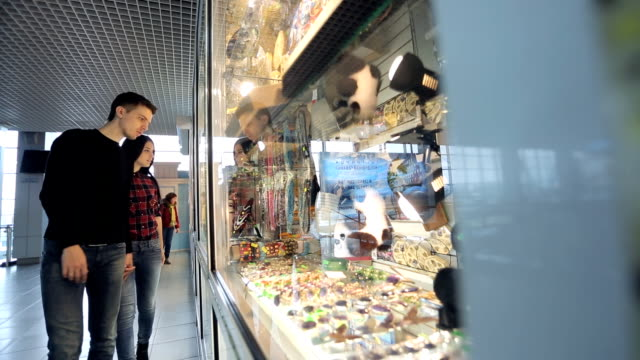 Pretty couple of people regards souvenirs in shop in airport video