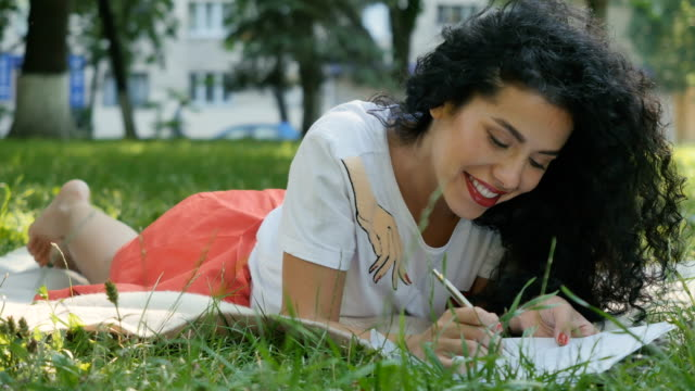 Pretty curly brunette relax on plaid in park and writes a letter video