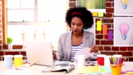 Pretty designer working at her desk with laptop video