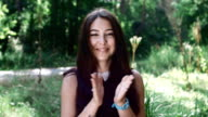 pretty girl claps her hands and rejoices in the forest video