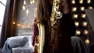Pretty girl in dress with saxophone on sitting on windowsill in retro room near window video