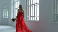Pretty girl in gorgeous red dress walking past the vintage windows with flowers and waves her hair, slow motion video