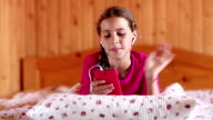 Pretty girl lies on the bed and communicates via smartphone video