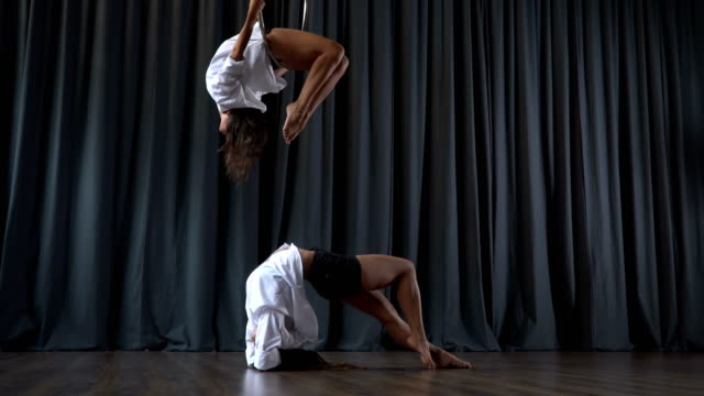 Pretty girl makes a tricks on aerial hoop and her friend warms up on floor video