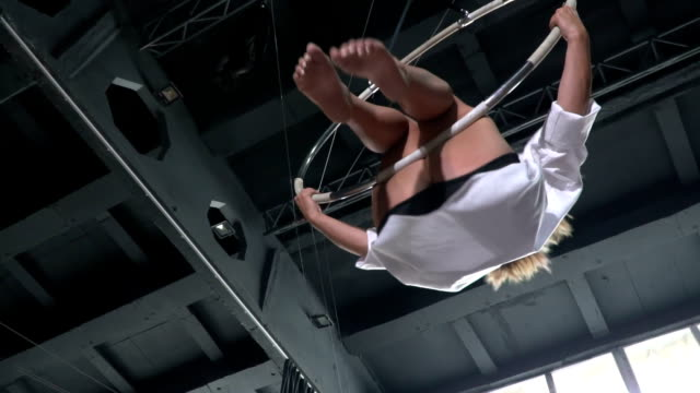 Pretty girl performs a trick on the aerial hoop in slowmotion video