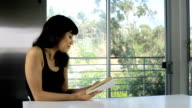 Pretty girl reading at kitchen counter video