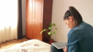 Pretty girl relaxed on the bed and using a digital tablet. video