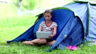 Pretty girl sits on grass near tourist tent and uses tablet computer video