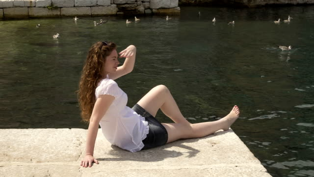 Pretty girl sitting on strand and and watching the sea video