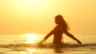 SLOW MOTION: Pretty girl standing up to waist in ocean and sprinkling the water video