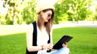 Pretty girl using tablet pc in the park on a sunny day video