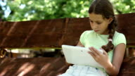 Pretty girl with tablet computer sits on swing bench video